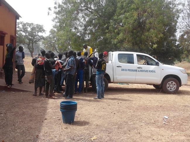 Des Burkinabè rapatriés de la Guinée se battant pour des friperies