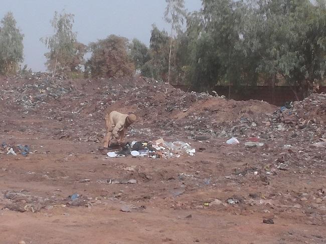 Ici, un fou fouille dans un tas d'ordures déposé malgré l'interdiction de jeter les ordures