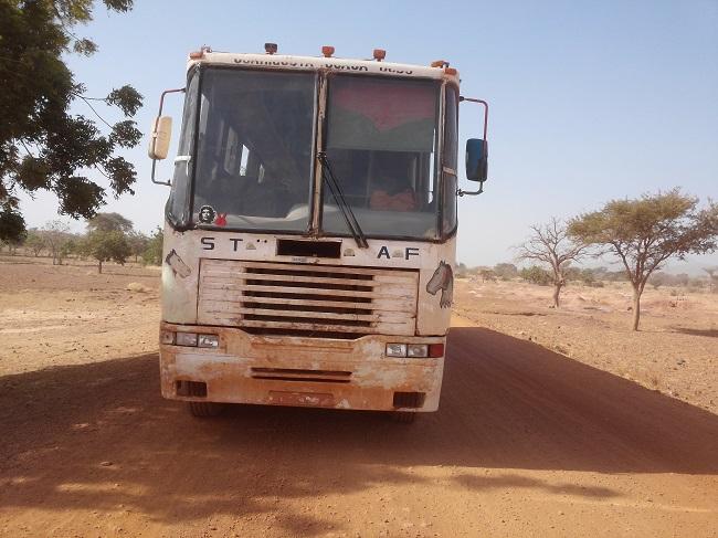 Une car de la compagnie STAF dans un village
